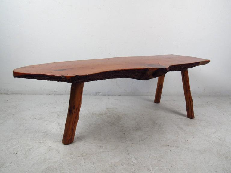 The unique natural wood finish on this vintage coffee table makes this the perfect addition to any home or business environment. This beautiful piece boasts a free form tree slab table top with splayed wood legs.  (Please confirm item location NY or