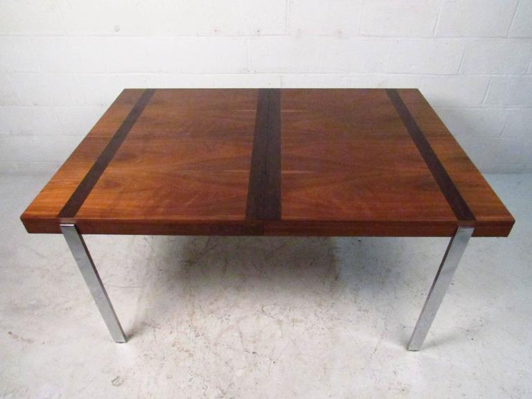 Vintage modern table by Lane with warm walnut grain accented by striking rosewood bands. Strong polished chrome legs add to the attractive modern look and make a lovely addition to kitchen, dining room, or small conference space.   (Please confirm