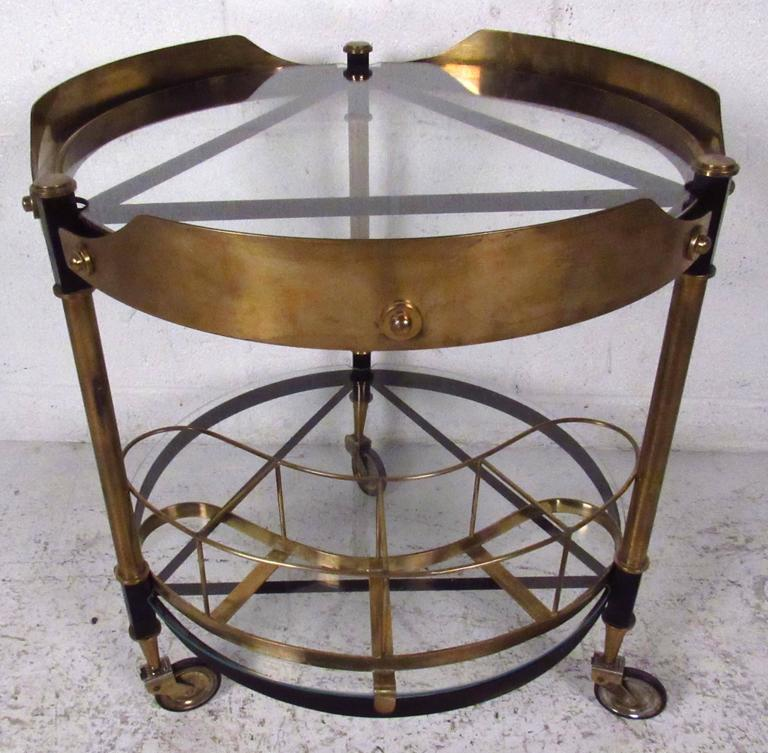 Vintage-modern serving cart featuring sculpted bronze and iron body with glass inserts. The stylish geometric approach to this midcentury Italian bar cart makes a striking and versatile addition to home or business.   Please confirm item location