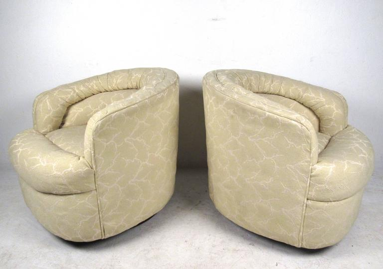 This stylish pair of vintage swivel lounge chairs features uniquely stitched original upholstery with comfortable stuffed seats. Barrel back seats and quality vintage construction add to the pair's appeal. Please confirm item location (NY or NJ).