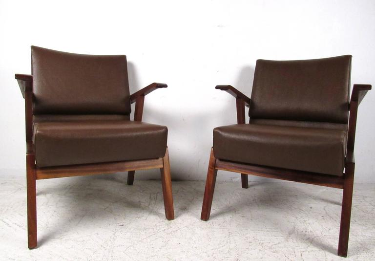 This comfortable pair of vintage Italian hardwood armchairs features a comfortable vinyl upholstered seat and backrest. Studded trim on back of seats, perfect pair for a variety of settings. Second pair available, contact for details. Please confirm
