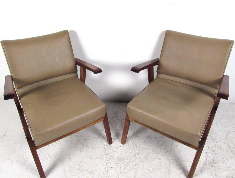 This uniquely styled pair of vintage armchairs make a comfortable and stylish addition to a variety of settings. Ideal for home or office, curved floating hardwood armrests compliment the ergonomic design of the seat back. Magazzini Generali. Please