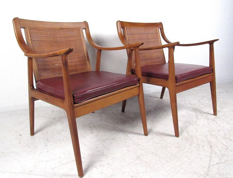 This stylish pair of cane back chairs make a comfortable vintage addition to any interior. Wonderfully crafted chair frames feature sloped style sculptural arm rests, upholstered seats, and tapered legs. Please confirm item location (NY or NJ).