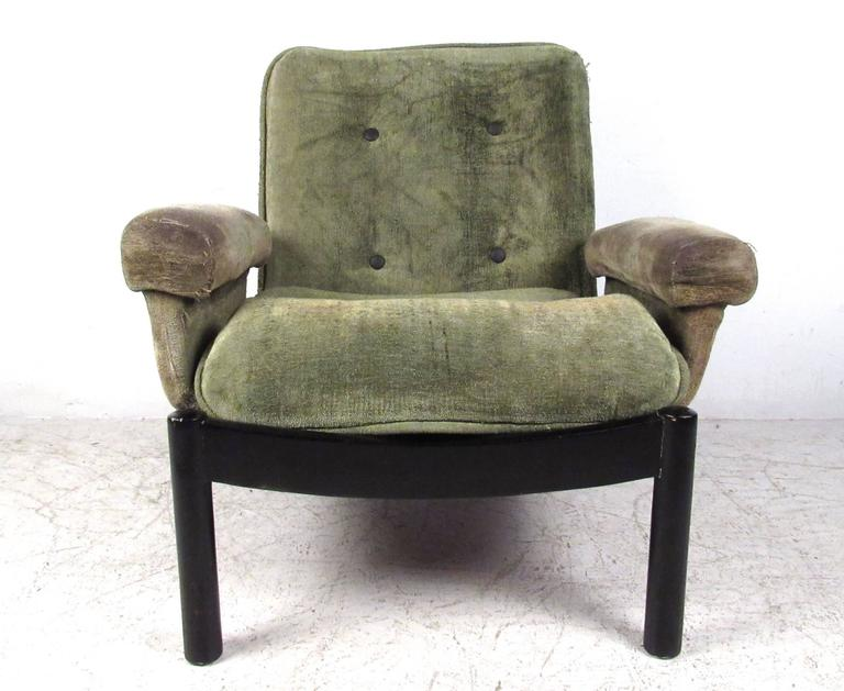 This uniquely designed vintage chair features a low slung style, complete with upholstered armrests, black lacquered frame,  and tufted seat back. Wide seat and plush seat back make this a comfortable addition to seating in any situation. Please