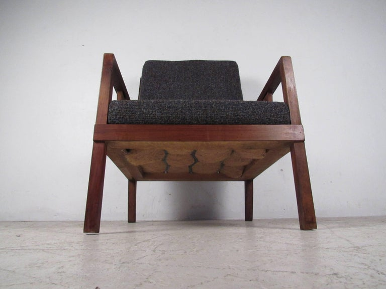 This retro walnut lounge chair features sculpted hardwood frame and quality vintage fabric. The unique design of this piece makes a comfortable and stylish addition to any setting. Please confirm location (NY or NJ).