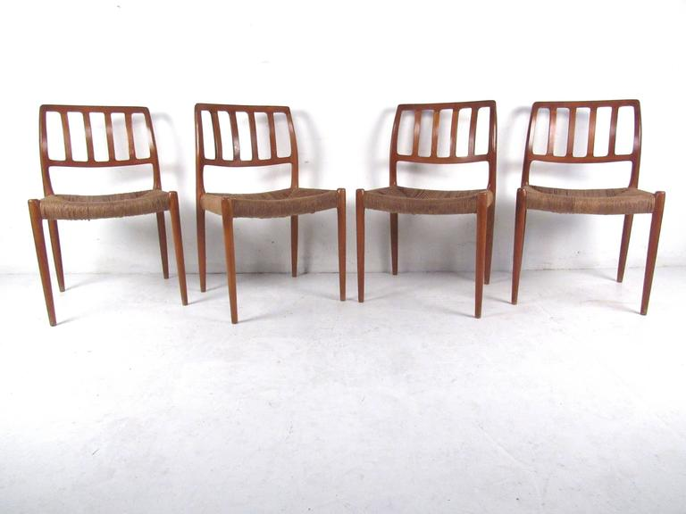 This gorgeous set of four dining chairs designed by N.O.Møller features woven rush seats and unique sculpted backs. These beautiful chairs make an impressive statement in any setting. Please confirm location (NY or NJ).