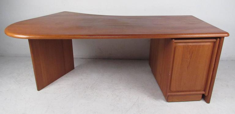 Well constructed contemporary styled teak desk with irregular shape top and finished back. Three drawer file cabinet is on casters and moves independent of the desk. Please confirm item location (NY or NJ) with dealer.