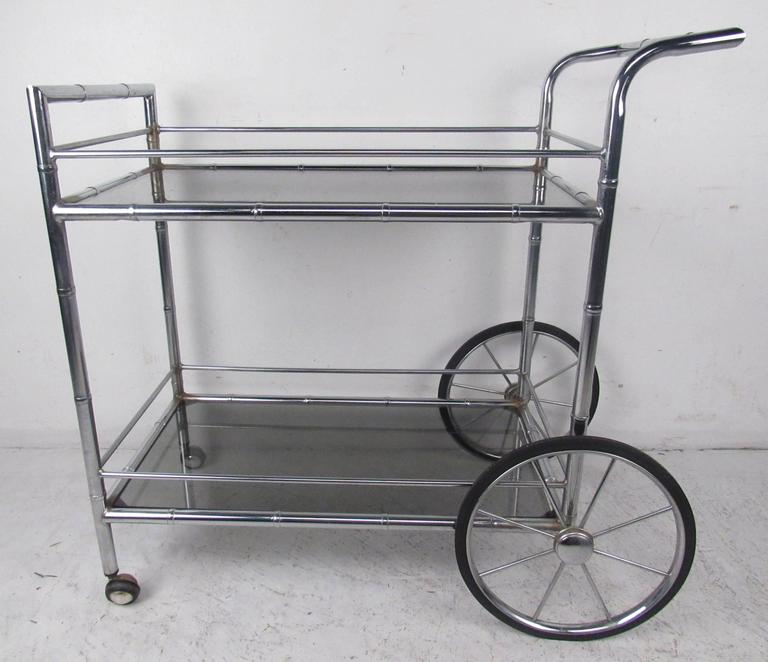 Chrome serving cart with bamboo motif and smoked glass shelves. Please confirm item location (NY or NJ) with dealer.