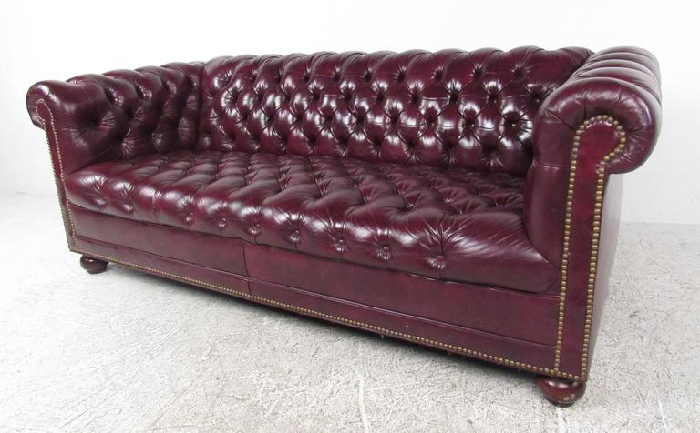 Matching pair of Classic Chesterfield sofas with deep tufted leather upholstery, large rolled arms and back, and decorative brass tack hardware. Excellent quality pair of sofa's perfect for home, hotel, or office seating.  Please confirm item