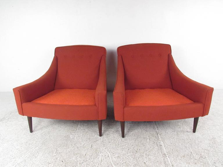 This stunning pair of Danish modern lounge chairs features wide and comfortable seat cushions with sculpted gradual armrests. Tufted upholstery and tapered legs add to the subtle style of this vintage set. Perfect additional seating for home or