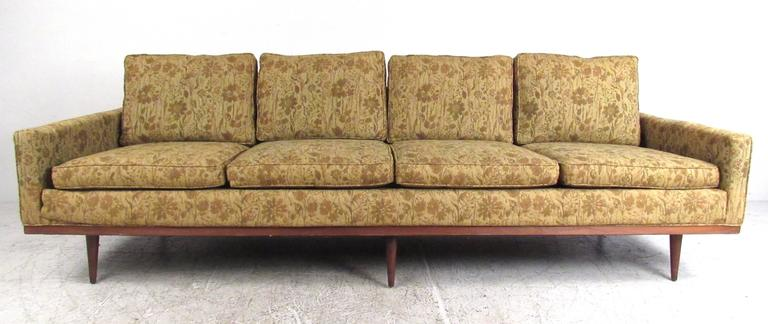 This exquisite vintage sofa features a stunning four seat design with six legs for added support. Wood trim, tapered post legs and classic Milo Baughman style add to the Mid-Century appeal of this long sofa. Please confirm item location (NY or NJ).