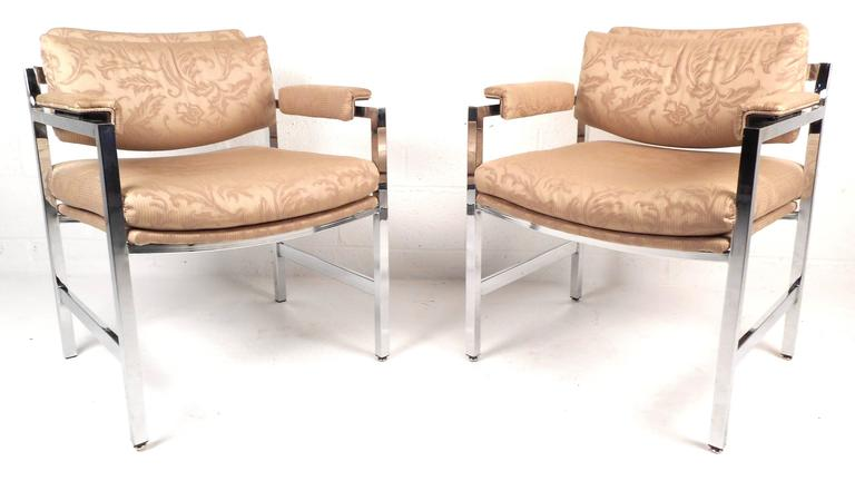 This elegant pair of vintage modern chrome frame arm chairs feature comfortable upholstered armrests with unique designs on the fabric. The thick padded seat and back rest ensure maximum comfort in any seating arrangement. The heavy chrome frame