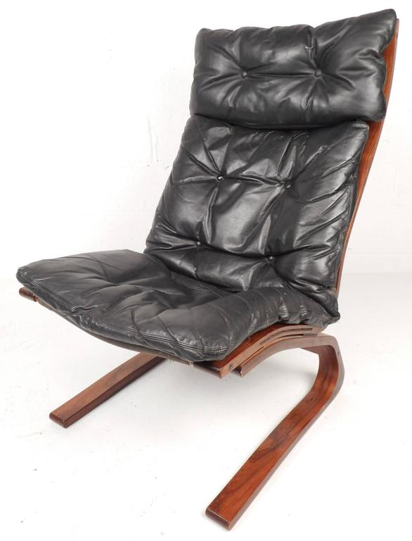 Stunning modern Ingmar Relling lounge chair and ottoman features a bent rosewood frame and tufted vintage leather. Unique design provides comfort without sacrificing style making it perfect for any interior. The ottoman's dimensions: 23.5 W 21 D 15