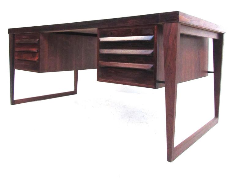 This stunning vintage rosewood desk features the masterful Mid-Century design of Kai Kristiansen. Unique sculpted drawer pulls, tapered floating sled legs, and dovetailed joints showcase the impeccable attention to detail taken in the construction