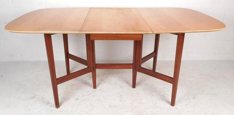 Stunning Mid-Century Modern drop-leaf dining table features solid walnut tapered legs and a vintage maple finished top. The stylish two-tone design and unique gate legs provide style and convenient storage in any setting. The dimensions when open