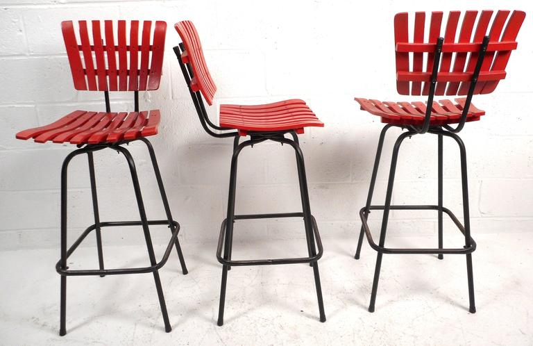 Lovely set of five vintage modern bar stools feature bright red slatted wood seats and backs, tubular iron bases, and a smooth swivel. The stylish design of Arthur Umanoff provides a unique look as well as comfort in any setting. Please confirm item
