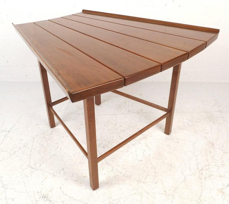 Gorgeous vintage modern slat bench/end table is made of solid walnut and features a uniquely shaped top with raised edges. The vintage walnut finish and stylish stretchers on the legs show quality craftsmanship. A versatile piece that offers various