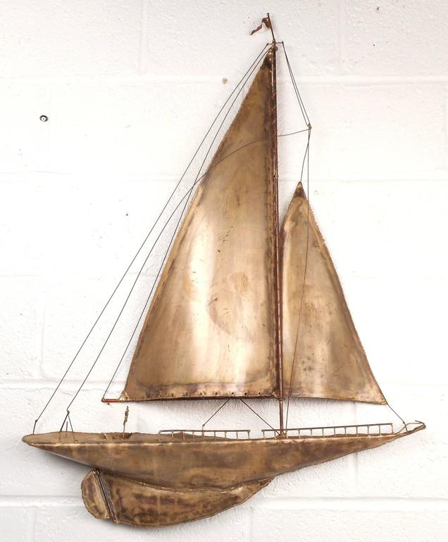 Stunning Mid-Century Modern metal sailboat wall art features intricate detailing from the mast to the keel. The unique design displays a miniature steering wheel, railing, rudder, and flag all patiently crafted by the designer. Perfect addition to
