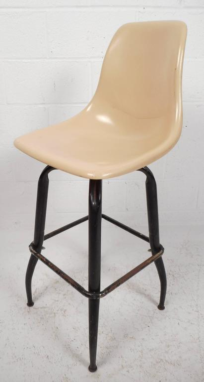 Beautiful set of five vintage modern swivel bar stools with plastic seats sculpted for optimal comfort. Sleek design with sturdy bent rod iron legs showing quality craftsmanship at its best. The wonderful ability to swivel and relax at the same time