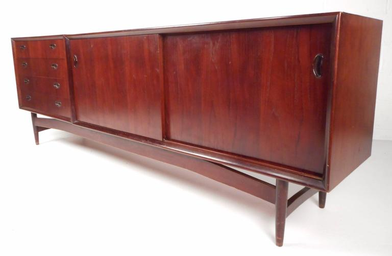 Impressive vintage modern Italian sideboard features two separate pieces that sit comfortably on top of a sculpted base with tapered legs. Sleek design with unique carved pulls, a finished back, and gorgeous wood grain. Plenty of storage space in