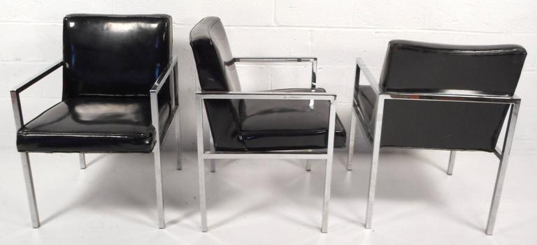 Beautiful set of four Mid-Century Modern dining chairs feature black vinyl and a heavy chrome frame. Sleek design with thick cushions and wide seating ensures comfort and style in any modern interior. Please confirm item location (NY or NJ).