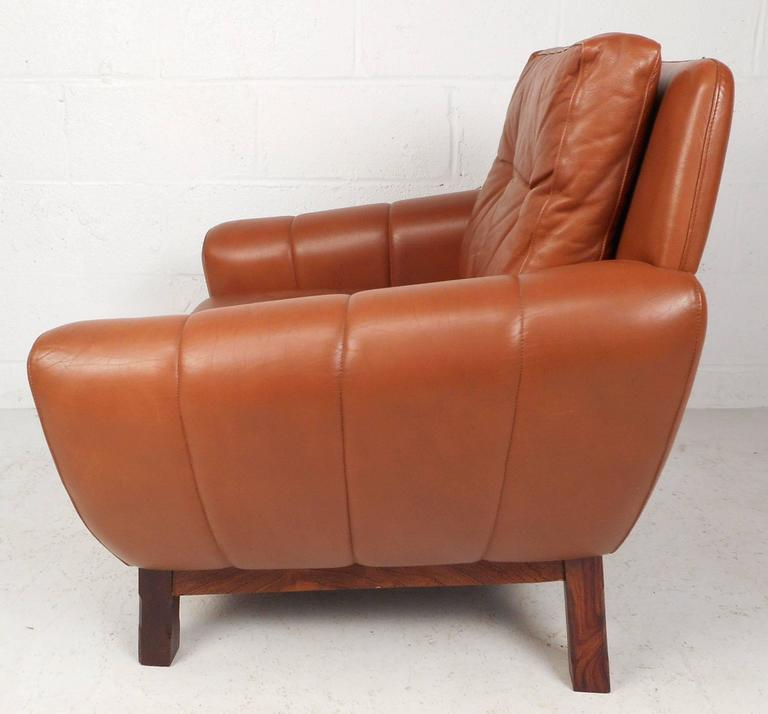 Beautiful vintage modern Danish lounge chair upholstered in orange leather. Comfortable design features wide seating, large armrests and thick cushions. The unique rosewood base and the stylish tufted backrest make it the perfect addition to any