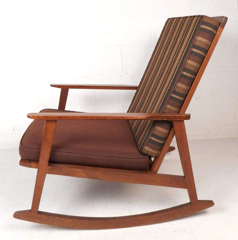 Lovely Mid-Century Modern rocking chair features a vintage walnut finish and sculpted arm rests. Sleek design with a smooth rocking motion. The unique high spindle backrest, vintage upholstery, and thick cushions are sure to compliment any modern