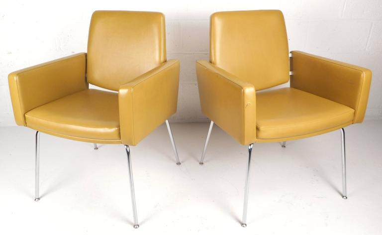 Stunning pair of vintage modern lounge chairs feature vinyl upholstery and unique bent rod chrome legs. The stylish floating backrest and thick padded seating offer comfort in any modern interior without sacrificing style. Please confirm item