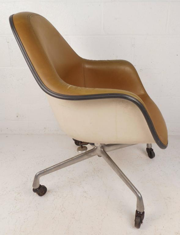 Beautiful vintage modern desk chair by Herman Miller features iconic strand fiberglass shell design with stitched vinyl upholstery. Stylish office chair has a chrome base with wheels ensuring comfort and convenience. Original stamp on bottom reads,