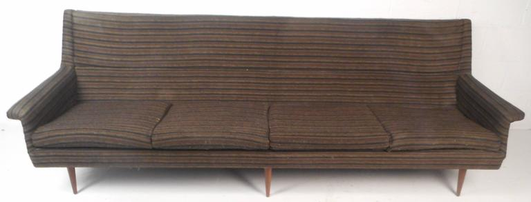 Attractive vintage modern sofa with unique wing shaped arm rests. Sleek design with clean mid-century line work combined with extreme comfort. Impressive sofa displays quality construction with six tapered and angled walnut legs ensuring sturdiness.