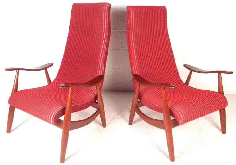 This beautiful pair of vintage modern lounge chairs feature a solid walnut frame with sculpted arm rests. Sleek design with unique angled legs, stylish curved stretchers, and a high backrest. Comfortable seating wonderfully upholstered in plush red