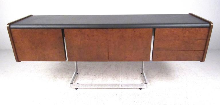Ste. Marie & Laurent credenza with black leather top, deep file drawer, three pencil drawers and center storage cabinet, cantilevered onto a polished chrome base. Please confirm item location (NY or NJ) with dealer.