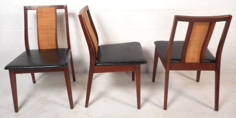 Elegant set of six vintage modern dining chairs feature solid walnut frames with black vinyl upholstery. Stylish design with cane in the center of the angled backrest and tapered legs. This sturdy and comfortable set of Mid-Century dining chairs
