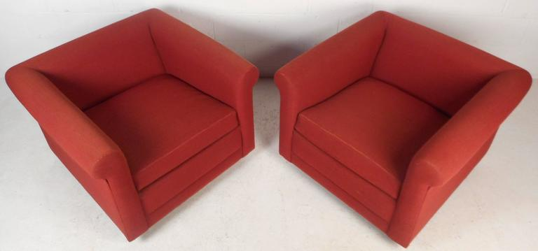 This beautiful pair of Mid-Century style lounge chairs feature bright red upholstery and thick padded cushions. Comfortable and stylish design with straight lines sits on top of four walnut legs. The wide seating and high arm rests make these the