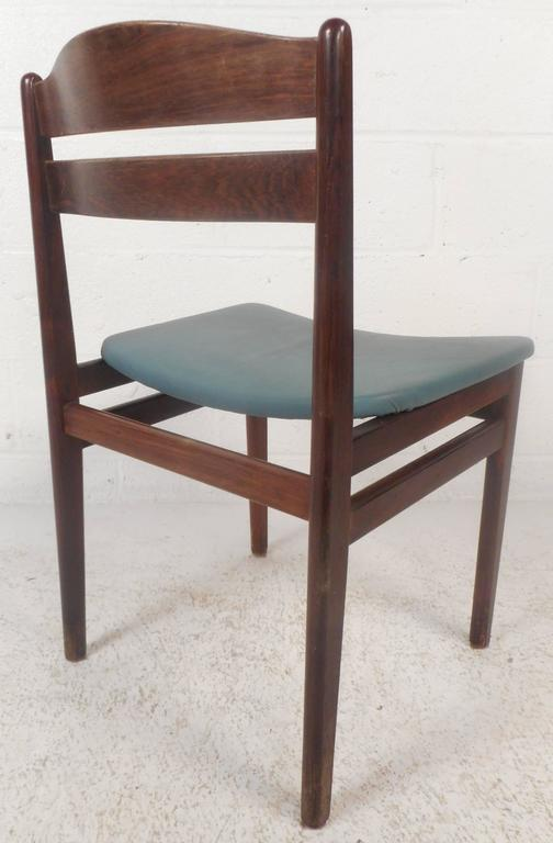 This stunning set of four vintage modern dining chairs feature a rosewood frame with leather seats. Sleek design with a sculpted backrest and stretchers connecting the legs for added sturdiness. This elegant Mid-Century set of dining chairs make the