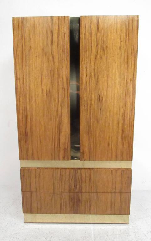Vintage wardrobe designed by Milo Baughman in rosewood with brass trim and ebonized shelves. Ample room for storage within a sleek casing.  Please confirm item location (NY or NJ) with dealer.