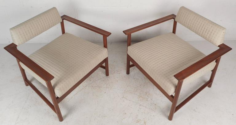 This beautiful pair of vintage modern lounge chairs feature an open frame design with a unique floating backrest. The solid walnut frame displays gorgeous wood grain and provides maximum sturdiness. Extremely comfortable pair with plush white