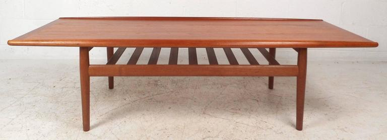 This beautiful vintage modern coffee table features unique raised edges on top and stylish tapered legs. The sleek design has a bottom slatted tier for additional storage. Quality construction with a rich walnut finish makes the perfect eye-catching