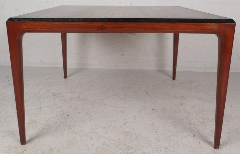 Beautiful vintage modern coffee table features stylish beveled edges with an ebonized strip that stretches all the way around the top. This sleek Mid-Century piece sits on top of four long and sturdy tapered legs. Versatile design with elegant