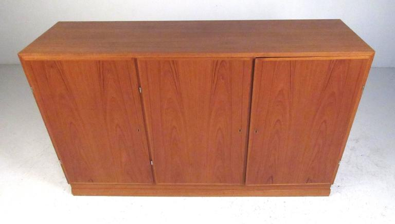 Danish modern three-door teak storage cabinet with beech interior consisting of (10) storage shelves and (4) felt lined trays. Please confirm item location (NY or NJ) with dealer.