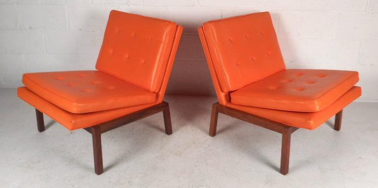 Exquisite pair of vintage modern lounge chairs covered in elegant orange tufted vinyl. This stunning pair features a solid walnut base with angled legs and thick padded cushions. The unique wide design has smaller rear legs so that this piece leans