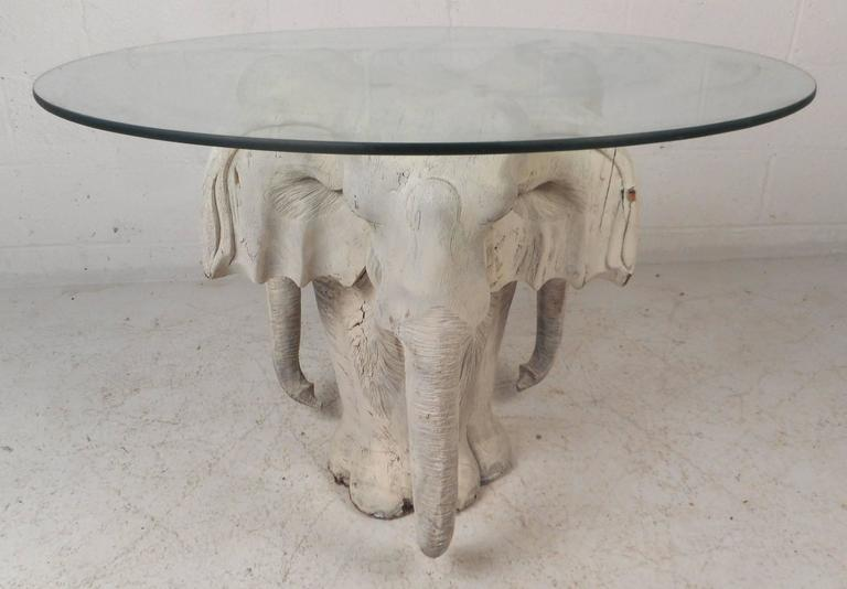 This beautiful vintage modern coffee table features a hand-carved wood base displaying an elephant on three sides. Unusual design with exquisite detail from the tusk to the ears. Sleek and Primitive piece has a round glass top with a tint of green.