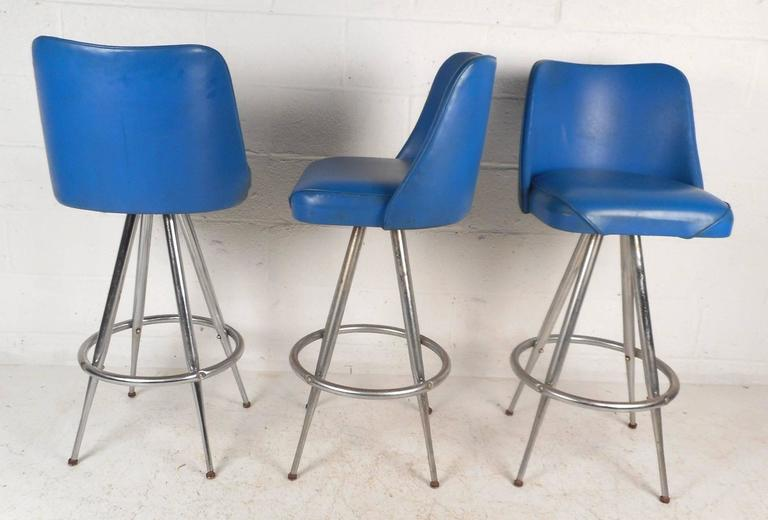 This beautiful set of four vintage modern bar stools feature elegant royal blue vinyl seats with the ability to swivel. Stylish design has tapered chrome rod legs that splay outward with a convenient round kick rest. Comfortable and sturdy chairs