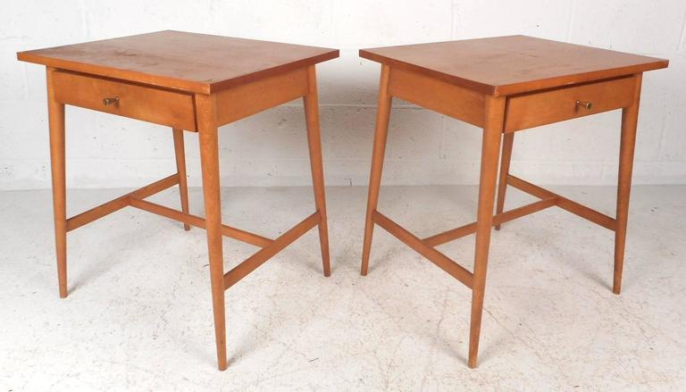 Beautiful pair of Mid-Century Modern nightstands with a vintage blonde maple finish. This stylish piece features one drawer with a unique conical brass pull. Sleek design with an oversized top and splayed tapered legs with stretchers for added