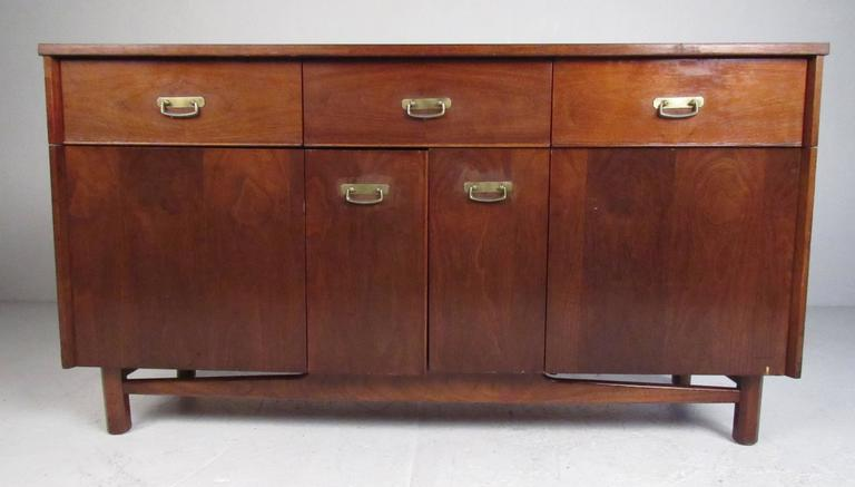 Mid-Century walnut credenza/buffet with durable laminate top, three top drawers and two bi-fold doors with shelf storage. Please confirm item location (NY or NJ) with dealer.