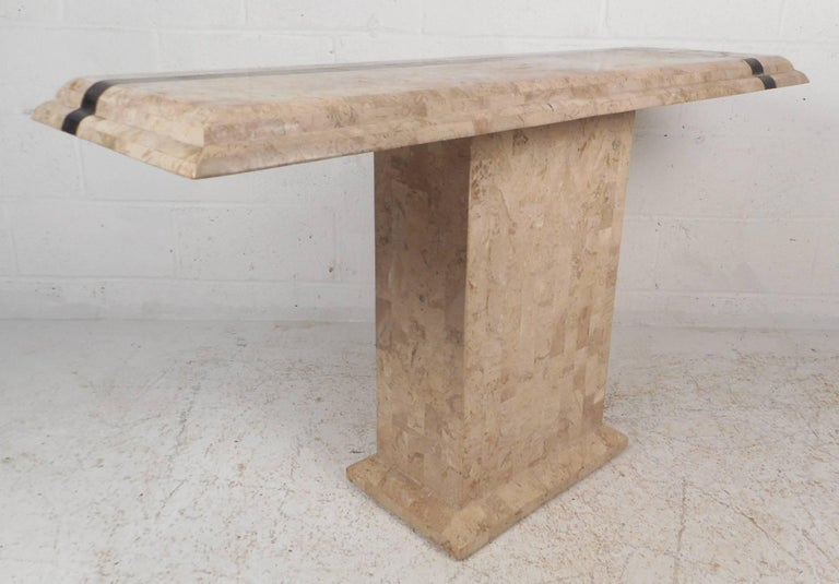 Stunning vintage modern hall table made of tessellated stone with elegant black inlays lined in a brass color. Unique tabletop with smooth beveled edges sits on top of a sturdy pedestal style rectangular base. Sleek design looks incredible in any