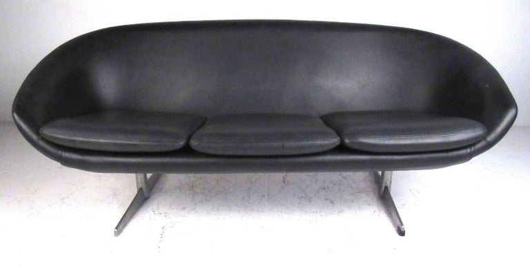 This sculptural molded urethane foam construction sofa is very light weight but durable. Vintage original black vinyl upholstery with brushed aluminium legs, it was manufactured by Swedish producer Overman for their U.S.A. division. Please confirm