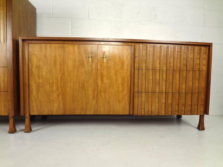 This handsome vintage modern bedroom set includes a high boy and a low dresser with unusual louvered fronts. The high boy features a hidden storage compartment on the top hidden by tambour doors and three hefty drawers on the bottom. The low dresser
