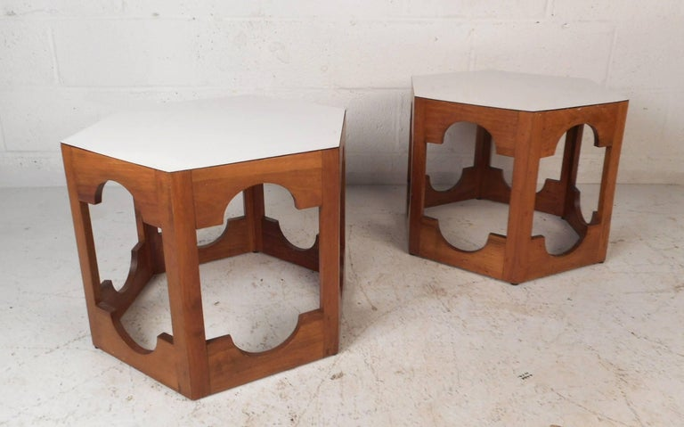 This beautiful pair of vintage modern end tables feature a white laminate top and a walnut base. Sleek design with unusual cut-out designs on all sides and a hexagonal shape. Versatile midcentury pieces function as pedestals, end tables, or simply a