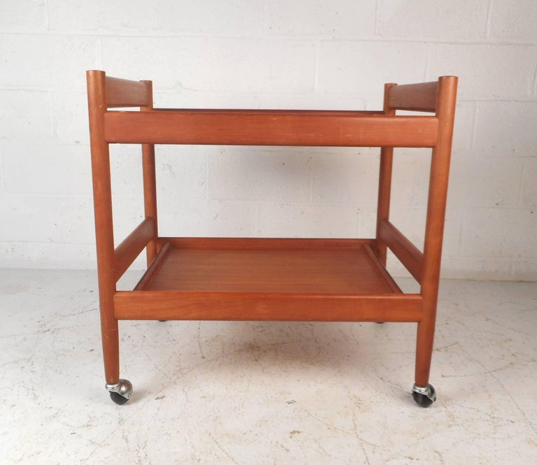 This beautiful vintage modern serving cart conveniently sits on top of four castors. This wonderful cart has handles on both sides and two large shelves for placing items. This functional and stylish piece has elegant teak wood grain throughout